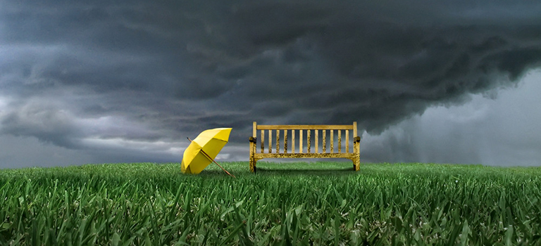 Storm clouds and yellow umbrella by bench