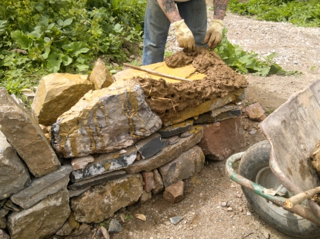 Sculpting the cob wall by hand