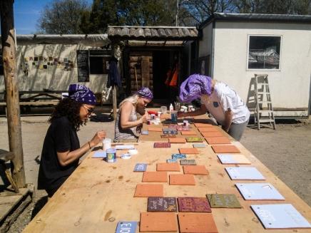 Participants painting handmade tiles